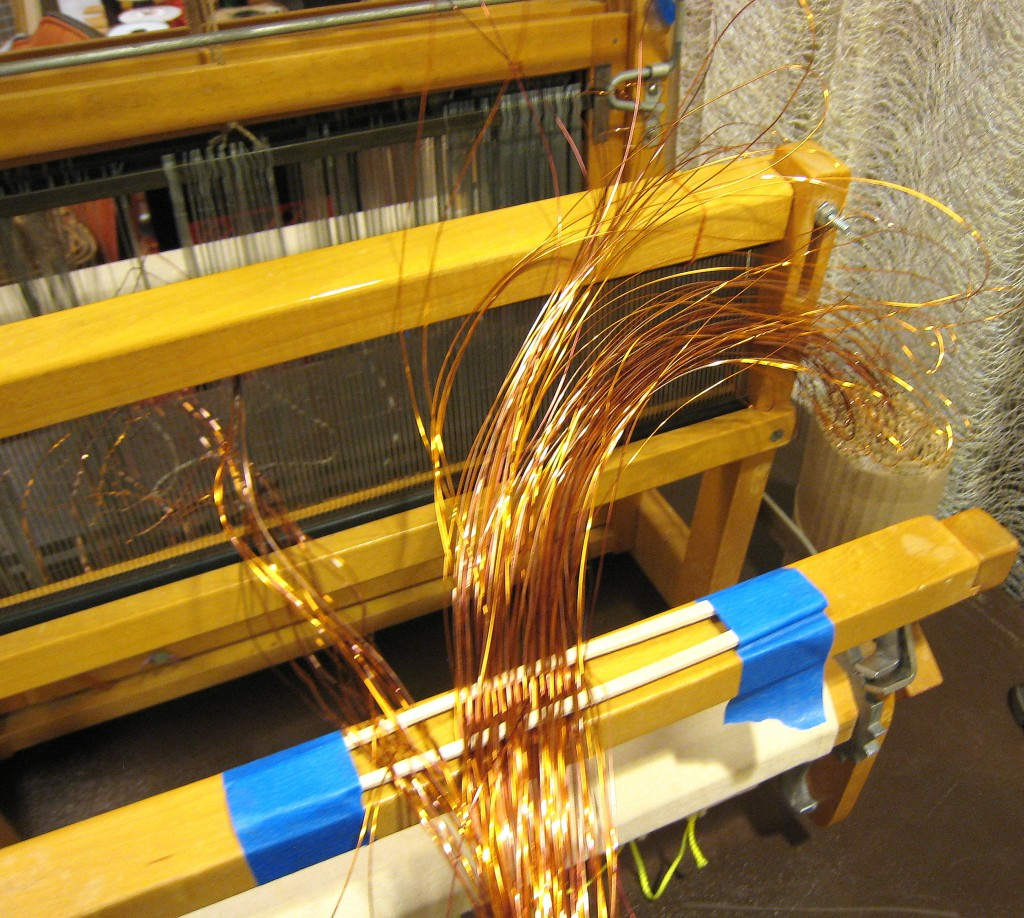 Here I was beginning to thread the wire warp into the reed--it was pretty jumpy and because it was shiny, it was hard to see what I was doing besides.