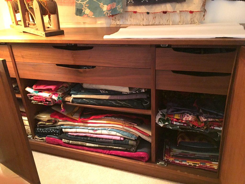 Textiles on shelves and in drawers in sideboard.